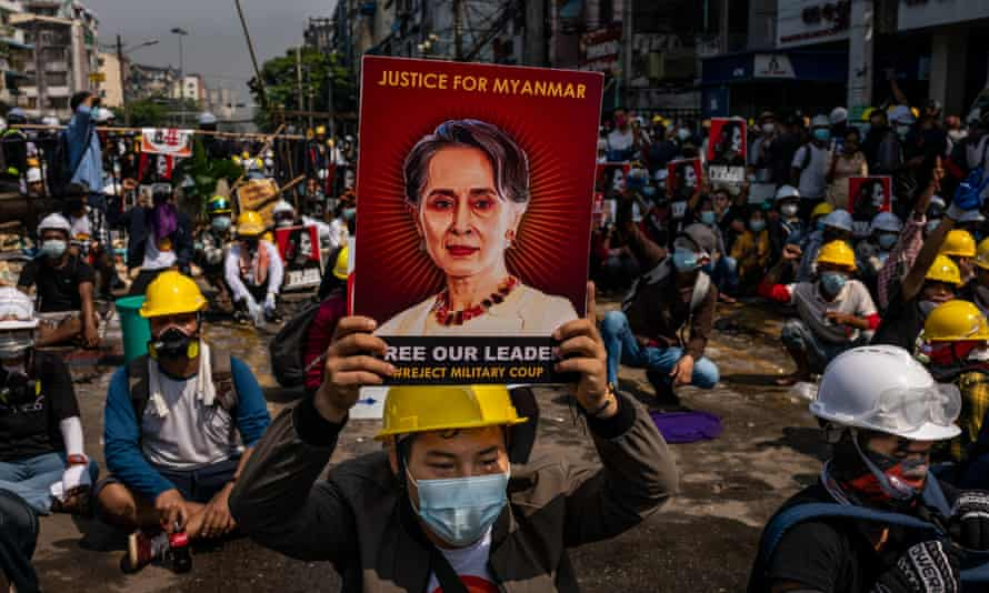 An anti-coup protester holds up a placard bearing an image of Aung San Suu Kyi in Yangon