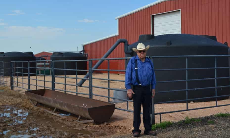 Bob Durham stands next to four of six rainwater collection tanks at his ranch near Abernathy, Texas.