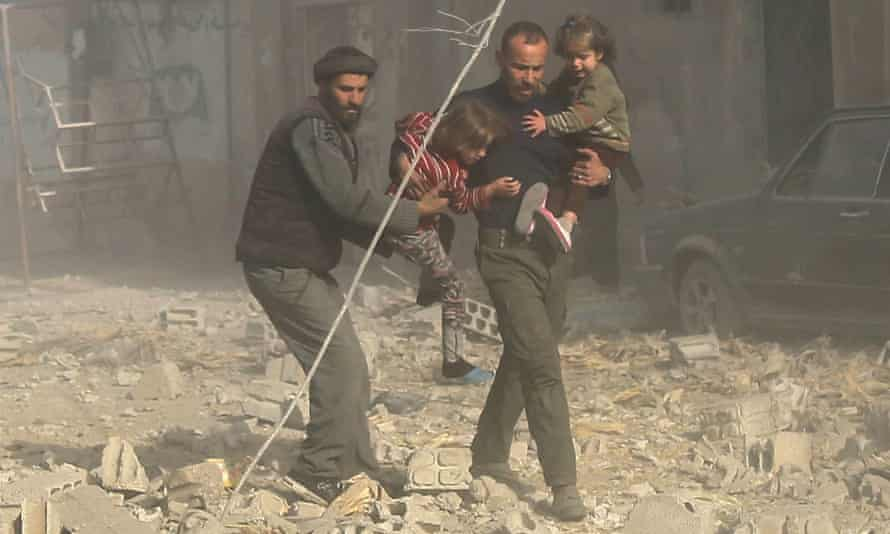 Syrians run with their children after an Assad-ordered air strike in Ghouta, Damascus.