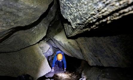 A woman crawls inside the Malham cave.