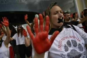 Anti-bullfight protesters hold up red painted hands