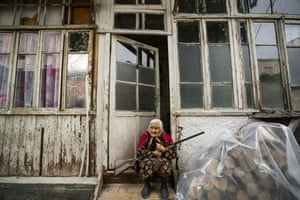 A woman sits at the entrance of her home with a rifle during the shelling near the city of Stepanakert in the disputed province of Nagorno-Karabakh.