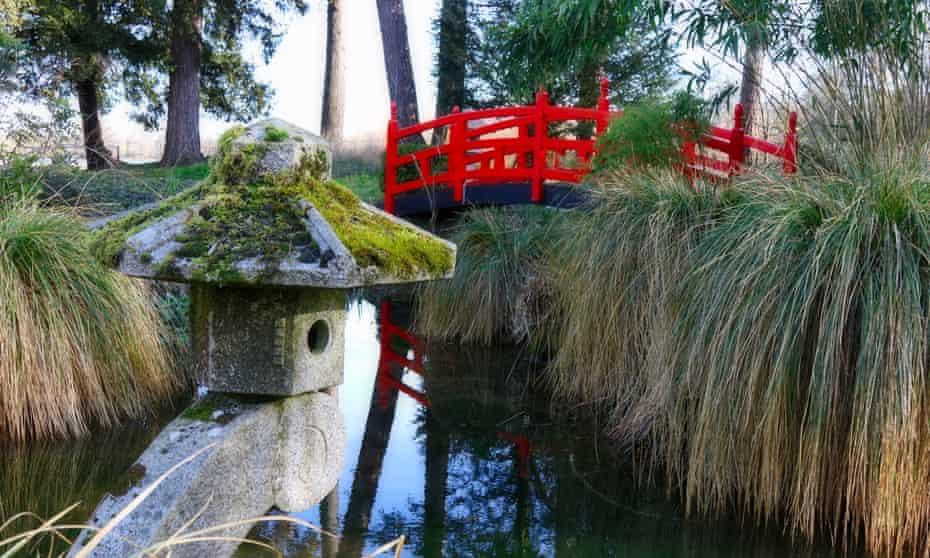 Red Japanese bridge over water in garden