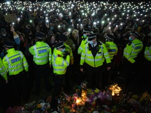 people hold candles as police stand in front