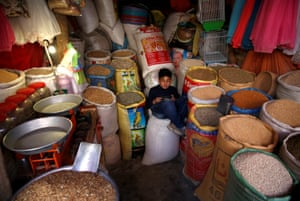 Afshin, 12, inside the shop where he works selling bird food