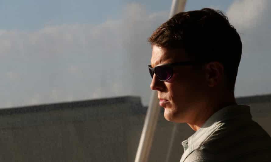 Jake Lacy as Shane, in sunglasses, looking cruel