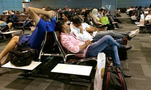 Passengers of cancelled flights wait in Hamad international airport in Doha.