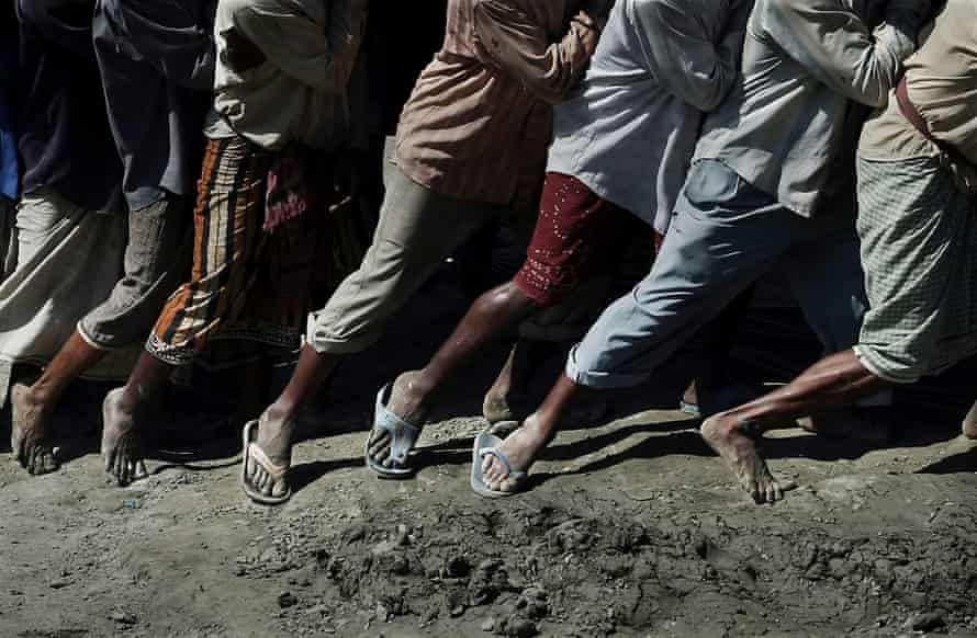 The legs and feet of labourers working in tandem to move an object on the beach.