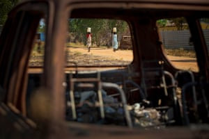 Two women walk passed a burnt-out car after fetching water from a water point that is being supported by UNICEF in the town of Malakal