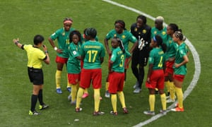 Cameroon players argue with referee Qin Liang after England's second goal
