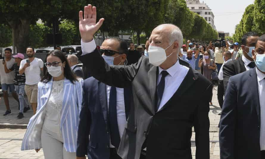 Kais Saied waves to bystanders as he strolls along the avenue Bourguiba in Tunis on 1 August.