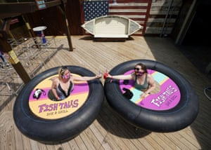 """Tracy Sandridge and Julie Brown of Baltimore pose with inner tubes on wheels dubbed """"bumper tables"""" designed to ensure social distancing when Fish Tales Bar & Grill eventually reopens in Ocean City, Maryland, U.S."""