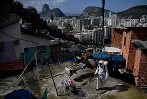 A volunteer disinfects a rooftop area inside Santa Marta Favela, in Rio de Janeiro, Brazil on 1 August, 2020, during the Covid-19 pandemic.
