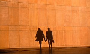 Two office workers silhouetted against a large orange wall