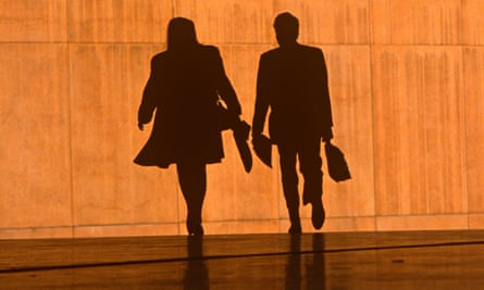 Two office workers silhouetted against a wall
