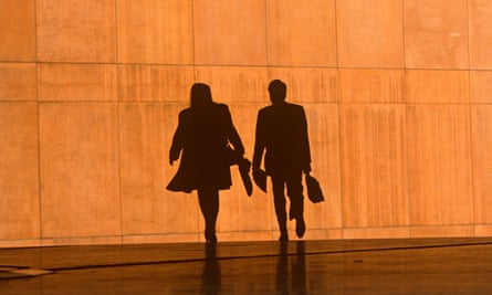 Two office workers silhouetted against the large orange wall of the Credit Lyonnais Bank at Broadgate in London.
