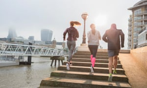 Runners running up sunny urban waterfront steps