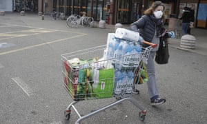A woman wearing a mask pushes a trolley after shopping in a supermarket in Casalpusterlengo, Northern Italy,