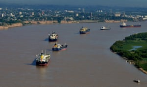 Ships line up in the Parana River as they wait to be loaded at the Port of Rosario in Argentina.