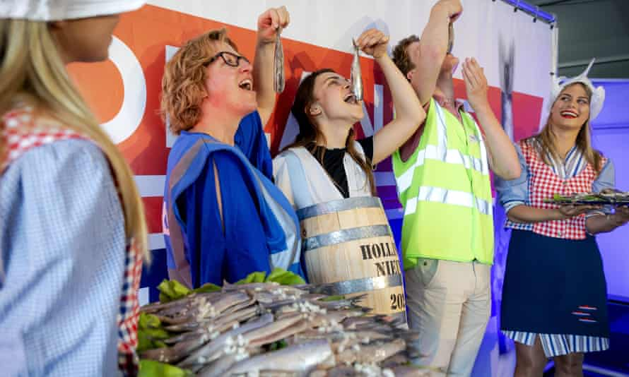 Vaccination centre staff pose with with herring in The Hague