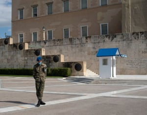 A Greek Presidential Guard wearing a protective face mask stands in front of the Unknown Soldier Tomb in Athens.