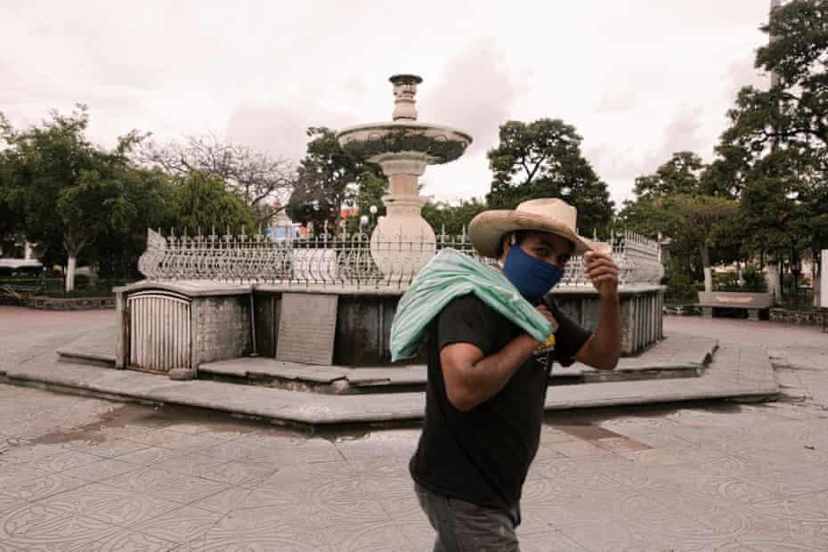 A man walks across Izúcar de Matamoros park wearing a mask.