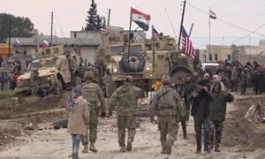 In this frame grab from video, Russian and Syrian military and local civilians gather next to a USn military convoy stuck in the village of Khirbet Ammu, east of Qamishli city, Syria, on Wednesday.