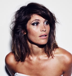 Gemma Arterton with bare shoulders, tanned, with pale pink lipstick and black and silver eye makeup