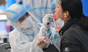 A health worker takes samples for a Covid-19 test from a woman at a testing station in Seoul.