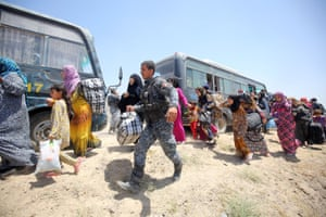 Iraqi forces help families near al-Sejar village, in Iraq's Anbar province, after fleeing the city of Fallujah, during a major operation by Pro-government forces to retake the city from the Islamic State (IS) group.