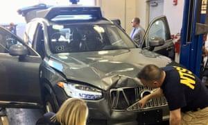 Investigators examine the Uber vehicle involved in the crash in Tempe, Arizona.