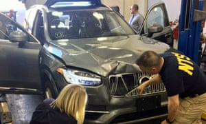 Federal investigators examine the self-driving Uber vehicle involved in a fatal accident in Tempe, Arizona.