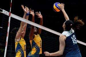 China's Liu Xiaotong spikes the ball as Brazil's Sheilla Castro De Paula Blassioli and Fabiana Claudino attempt to block.