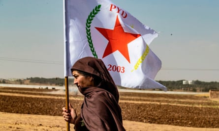 A Syrian Kurdish woman waves the flag of the Democratic Union Party during a demonstration near the town of Tel Arqam near the Turkish border on 6 October 2019.