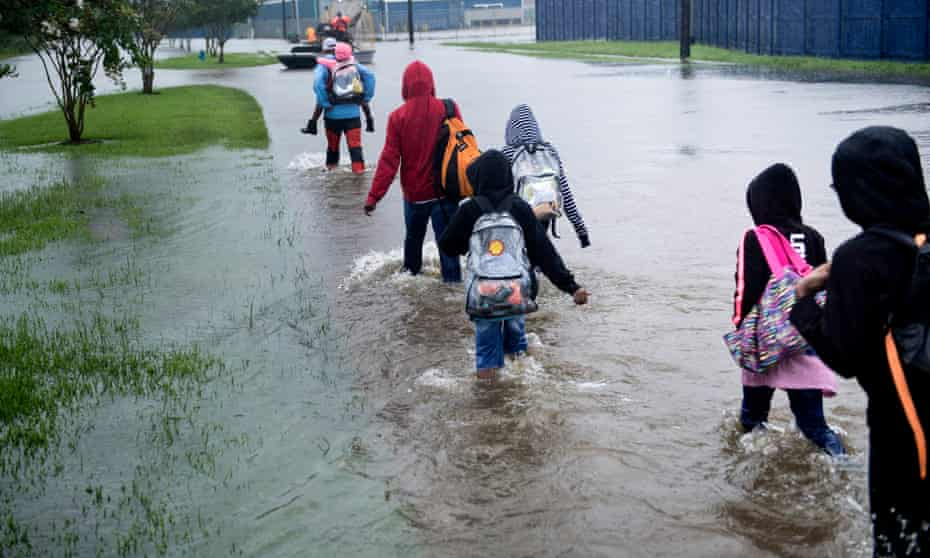 People walk to a Harris County Sherif airboat while escaping a flooded neighborhood during the aftermath of tropical storm Harvey.