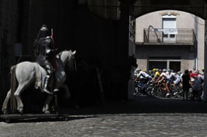 The pack with Geraint Thomas, wearing the yellow jersey, rides past a statue during the 218km 16th stage between Carcassonne and Bagnères-de-Luchon.