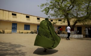 An Indian Muslim woman walks toward a polling station to cast her vote