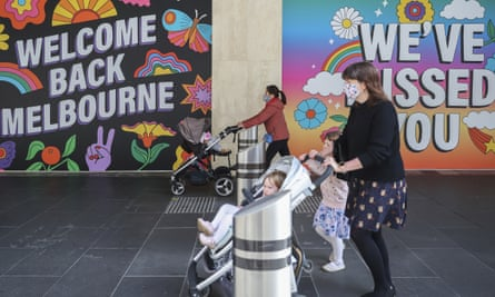 two women with strollers in front of welcome back melbourne signs