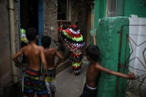 Children look at a reveller during the traditional Folia de Reis celebration to mark the arrival of the three wise men in the Santa Marta slum.