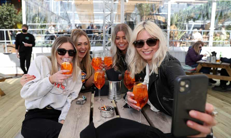 A group of women take a selfie as they enjoy a drink at a bar in Manchester.
