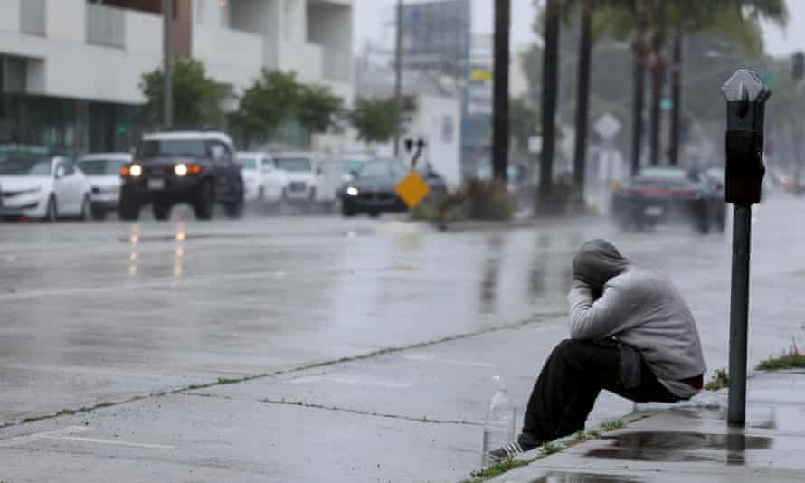 A homeless man sits on a curb in the pouring rain in the Mar Vista neighborhood of Los Angeles.