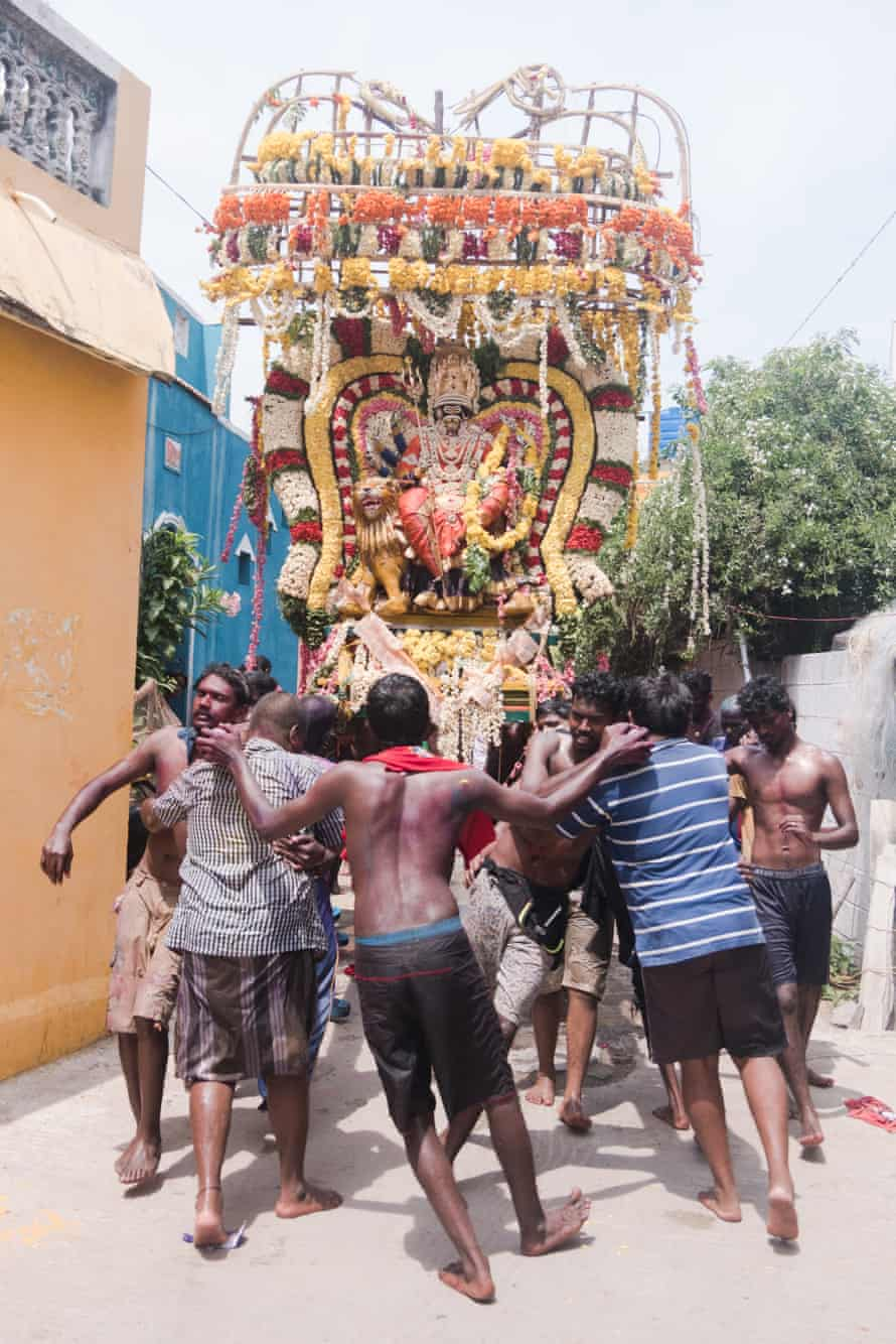 Men carry a devotional chariot through the streets en route to the beach in Mahabalipuram.
