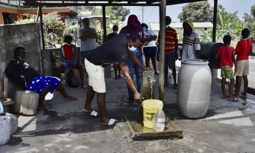 People collect clean water from a standpipe in Wallilabou after volcanic ash contaminated their supplies