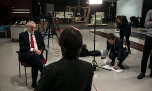 Jeremy Corbyn giving an interview to ITV's Robert Peston at the National Transport Design Centre in Coventry, where Corbyn gave his speech. Seumas Milne, Corbyn's strategy and communications chief, listens in, consulting his notes on the floor.