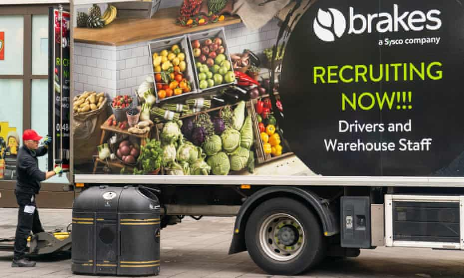An advert for drivers and warehouse staff is displayed on the side of a lorry as a driver makes a delivery in central London.