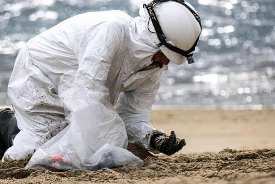 A worker in a protective suit cleans up Huntington Beach, bending over the sand