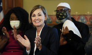 Kim Reynolds reacts after signing the executive order on Wednesday.