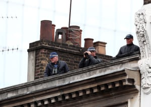 Police officers monitor the proceedings from a roof overlooking Southwark Cathedral
