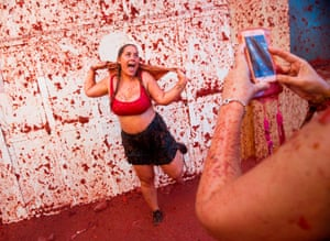 A woman covered in tomatoes poses for a selfie at La Tomatina in Spain