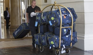 Luggage belonging to the Australia team is wheeled out of their hotel in Cape Town as the team prepare to depart.
